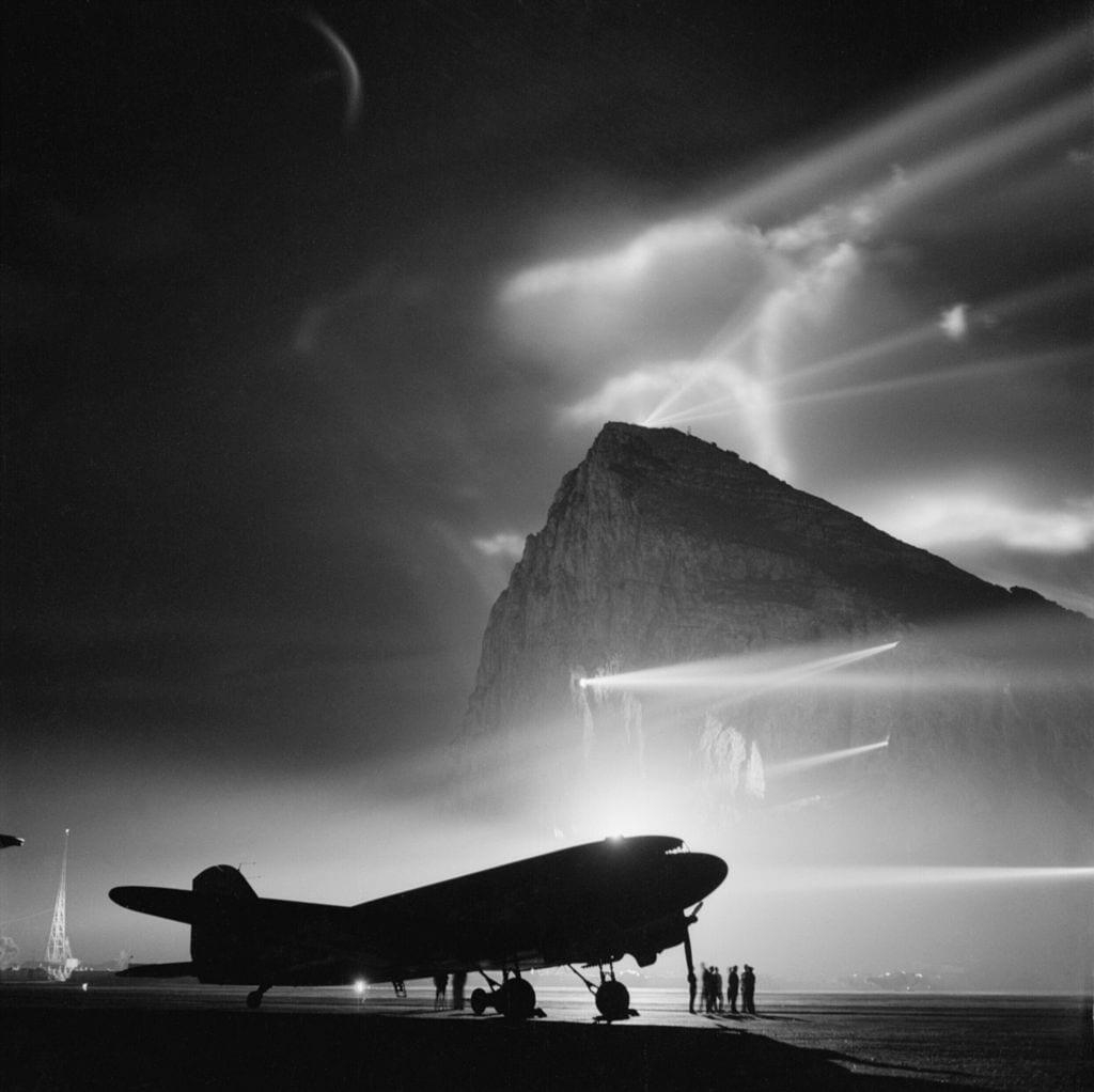 Douglas_DC-3_of_BOAC_at_Gibraltar,_silhouetted_by_searchlights_on_the_Rock